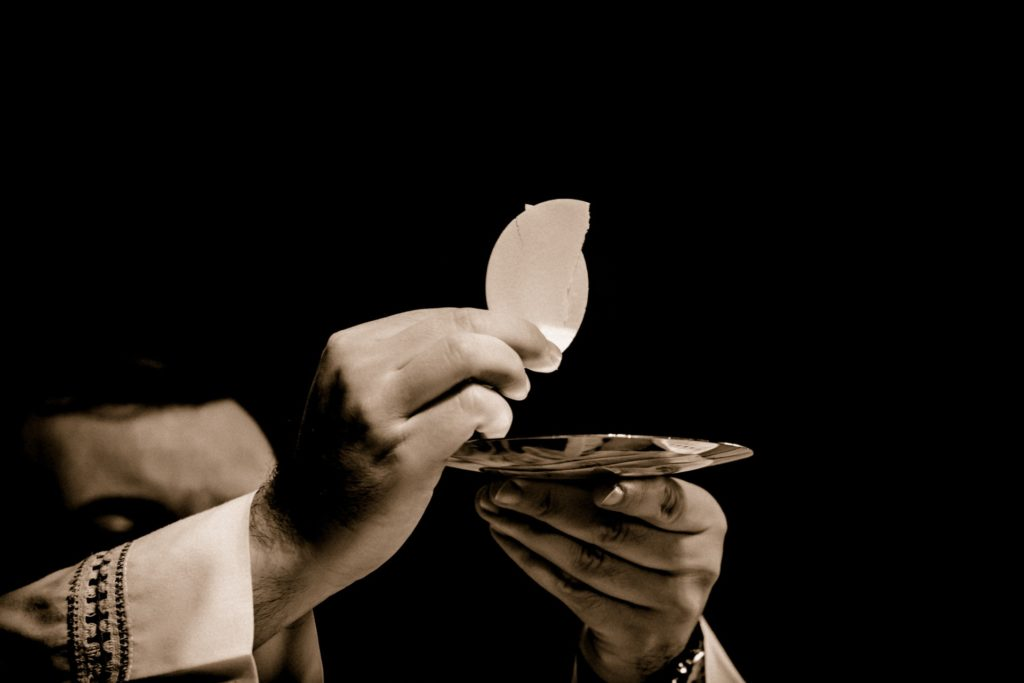 Hands of priest holding up the Eucharist