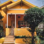 Bright yellow house with steps to front door and small tree